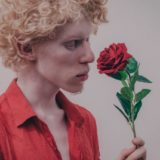 バラの香りを嗅ぐ男性