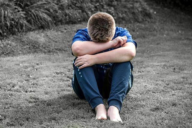 顔を膝にうずめている男の子