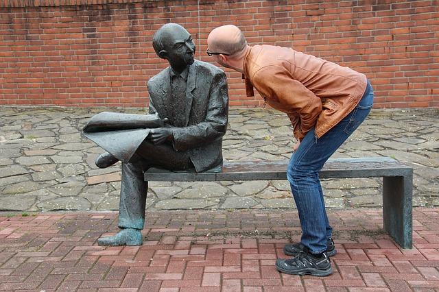 銅像に向かって話しかけている男性