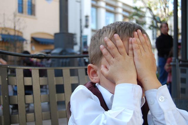 顔を両手で覆う男の子